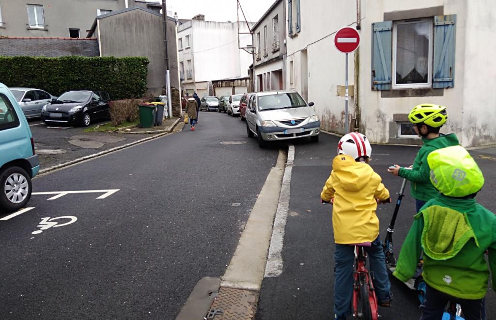 Trois jeunes enfants, à vélo sur un trottoir complètement occupé par des véhicules en stationnement